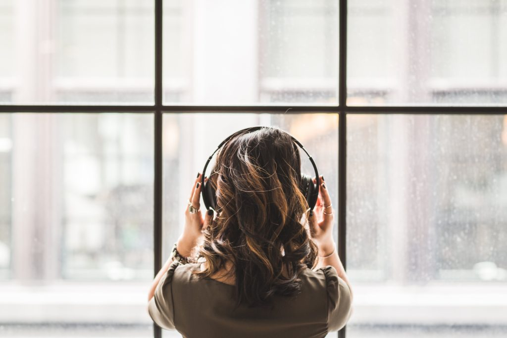 woman with headphones at window